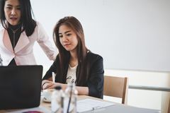 Two women participate business meeting. Two Asian businesswomen discussing about their project while participating in company meeting. Young startup Stock Image