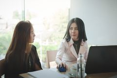 Two women participate business meeting. Two Asian businesswomen discussing about their project while participating in company meeting. Young startup Stock Images