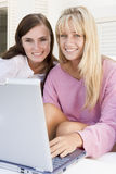 Two women on patio using laptop Royalty Free Stock Images