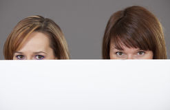 Two women peeking over white banner Royalty Free Stock Photos