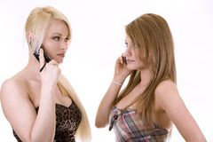 Two women on the phone. Two pretty woman on white isolated background talking on the phone Stock Image