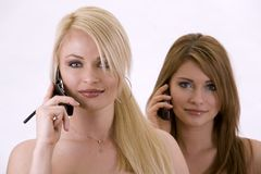 Two women on the phone. Two pretty woman on white isolated background talking on the phone Stock Images