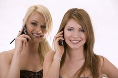 Two women on the phone. Two pretty woman on white isolated background talking on the phone Royalty Free Stock Images