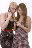 Two women on the phone. Two pretty woman on white isolated background talking on the phone Royalty Free Stock Image
