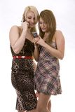 Two women on the phone. Two pretty woman on white isolated background talking on the phone Stock Photography
