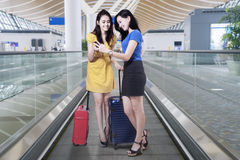 Two women with phone on the escalator Royalty Free Stock Images