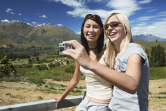 Two Women Photographing Themselves Against Countryside Fence Royalty Free Stock Images