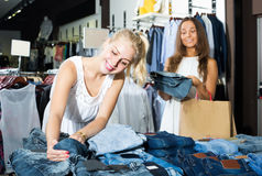 Two women picking new pair of jeans in fashion department. Two young happy american women picking new pair of jeans in fashion department Stock Images