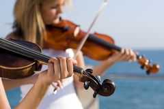 Two women play violin on beach Stock Photos