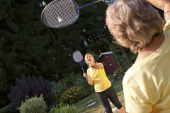 Two women playing badminton. In the garden Stock Image
