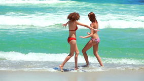 Two women playing at the beach. Splashing each other stock footage