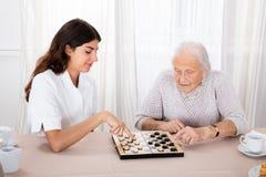 Two Women Playing Checkers Game. Senior Woman Playing Checkers Game With Young Nurse On Table royalty free stock photo