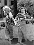 Two women playing a game of potato sack racing Stock Photos
