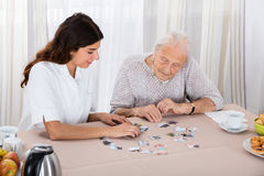 Two Women Playing Jigsaw Puzzle. Elder Woman Playing Jigsaw Puzzle On Table With Her Nurse Stock Photo