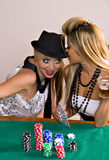 Two women playing poker. Two beautiful young women caucasian and asian playing poker with chips and cards Stock Photography