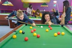 Two women playing pool stock photos