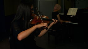 Two women playing a violin and piano. In music studio 4k stock video