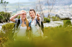 Two women pointing and looking ahead while hiking. Friends hiking together outdoors exploring the wilderness and having fun royalty free stock image