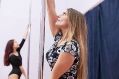 Two women pole dance practicing at studio Stock Photography