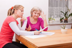Two women pondering over documents royalty free stock photo