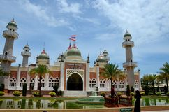 Two women pose at Pattani central mosque courtyard with pond minarets and Thai flag Thailand stock photography