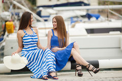 Two women posing in the Harbor in the background yachts Royalty Free Stock Images
