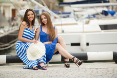 Two women posing in the Harbor in the background yachts. Two young beautiful women brunette with long straight hair,cute smile,dressed in tunics of blue and blue Stock Photo