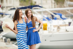 Two women posing in the Harbor in the background yachts Stock Photos