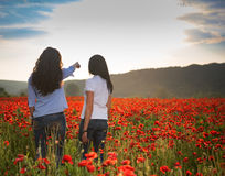 Two women posing on the poppy field Royalty Free Stock Image