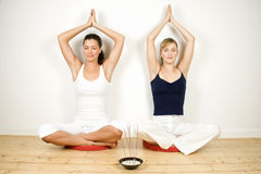 Two women practicing yoga. Stock Image