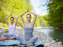 Two women are practicing yoga by the mountain river Stock Photography