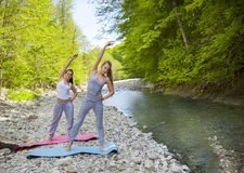 Two women are practicing yoga by the mountain river Royalty Free Stock Image
