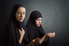 Two women pray. On dark background Royalty Free Stock Photography