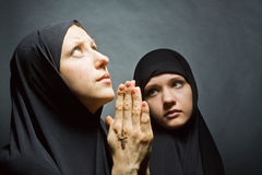 Two women pray. On dark background Royalty Free Stock Images