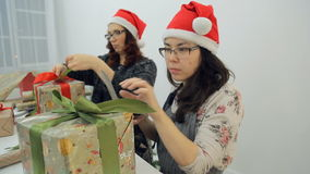 Two women prepare new year presents for Christmas holidays inside. Asian brunette woman in apron, flower sweater sits cuts green ribbon with scissors on stock footage