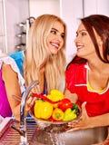 Two women preparing food at kitchen Stock Photos