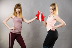 Two women presenting sportswear trainers shoes. Two happy sporty smiling women presenting sportswear trainers red shoes, comfortable footwear perfect for workout Stock Image