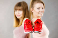 Two women presenting sportswear trainers shoes. Two happy sporty smiling women presenting sportswear trainers red shoes, comfortable footwear perfect for workout Royalty Free Stock Photo