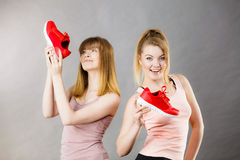 Two women presenting sportswear trainers shoes. Two happy sporty smiling women presenting sportswear trainers red shoes, comfortable footwear perfect for workout Stock Photography