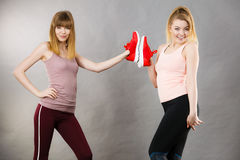 Two women presenting sportswear trainers shoes. Two happy sporty smiling women presenting sportswear trainers red shoes, comfortable footwear perfect for workout Royalty Free Stock Photography