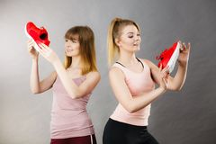 Two women presenting sportswear trainers shoes. Two happy sporty smiling women presenting sportswear trainers red shoes, comfortable footwear perfect for workout Stock Photo