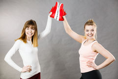 Two women presenting sportswear trainers shoes. Two happy sporty smiling women presenting sportswear trainers red shoes, comfortable footwear perfect for workout Royalty Free Stock Photos