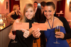 Two women presenting theatre or movie tickets Stock Images