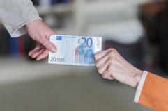 Two women pulling on a banknote. Generational conflict, old woman and young woman pulling on a euro banknote Stock Images