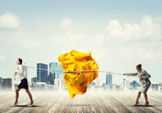 Two women pulling with effort big crumpled ball of paper as creativity sign Royalty Free Stock Photo