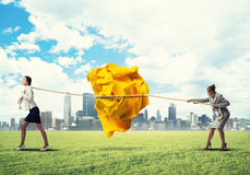 Two women pulling with effort big crumpled ball of paper as creativity sign Stock Photography