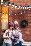 Two women in purple knitted hats. Purple infinity scarf and blue jeans make posing with brick wall and Christmas garland on the background Royalty Free Stock Photos