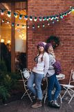 Two women in purple knitted hats. Purple infinity scarf and blue jeans make posing with brick wall and Christmas garland on the background Stock Photography