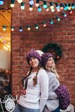 Two women in purple knitted hats. Purple infinity scarf and blue jeans make posing with brick wall and Christmas garland on the background Stock Image