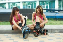 Two women put on kangoo jumping boots and smiles. beautiful girls wearing shoes before outdoor fitness workout. Active lifestyle concept stock photos